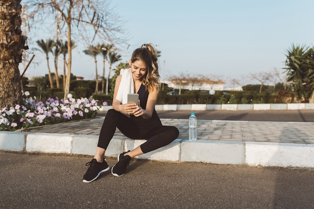 熱帯都市の通りに外に座っているスポーツウェアで幸せなうれしそうな若い女性。電話でのチャット、積極性、真の感情、健康的なライフスタイル、フィットネス、トレーニングの表現