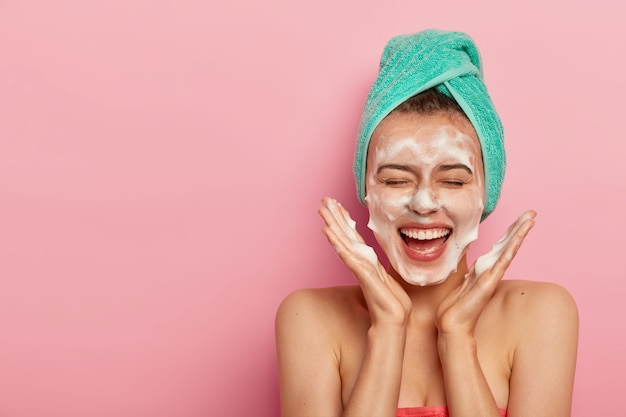 Happy joyous young girl spreads palms over face, washes face with soap, has fun in bathroom, pampers skin, wears wrapped towel on head, expresses positive emotions