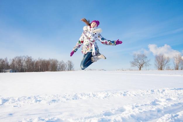 ウィンターパークで幸せなジャンプの女の子