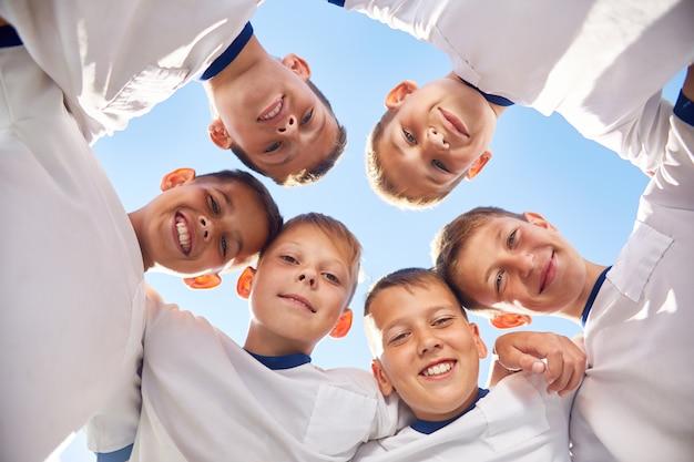 Счастливая юношеская футбольная команда в круге