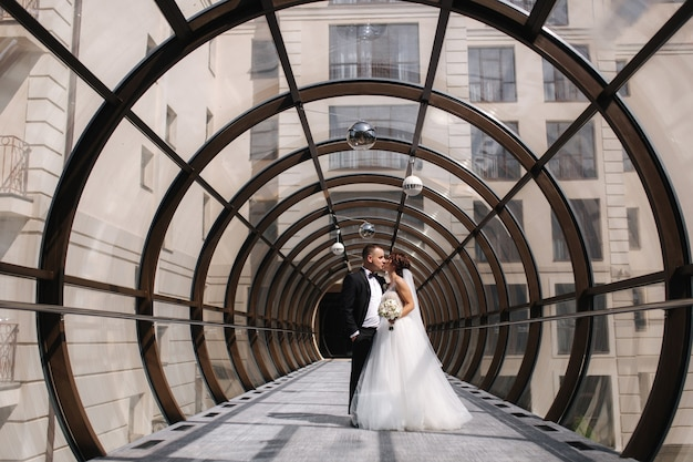 Happy just married couple walking beautiful round window in wedding day.