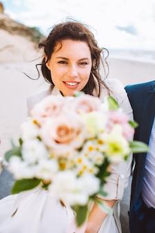 花とビーチで軽いドレスを着て幸せなちょうど結婚した中年の花嫁は夏の日に楽しんでいます。