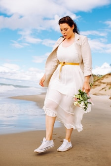 Happy just married middle age bride wearing light dress and sneackers walk at beach with flowers and have fun on summer day.