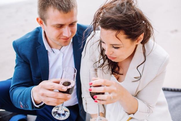 幸せなちょうど結婚した中年夫婦はワインでビーチで祝い、夏の日に楽しんでください。