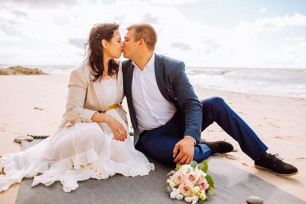 幸せなちょうど結婚した中年のカップルはビーチで歩き、夏の日に楽しんでいます。男と女はお互いにキスします。