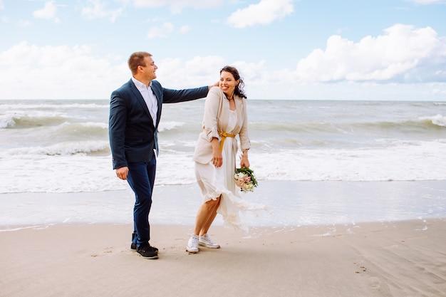 Счастливые молодожены среднего возраста гуляют на пляже и веселятся в летний день.