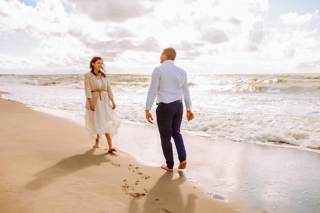 幸せなちょうど結婚した中年のカップルはビーチで歩き、夏の日に楽しんでいます。