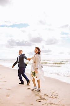 Happy just married middle age couple walk at beach and have fun on summer day.