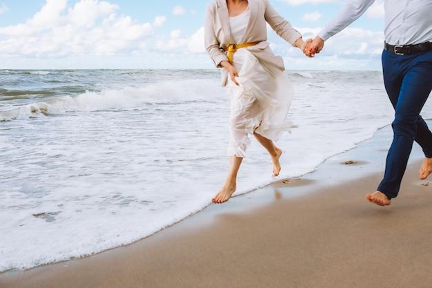 幸せな結婚したばかりの認識できない中年のカップルがビーチを歩いて、夏の日に楽しんでいます。