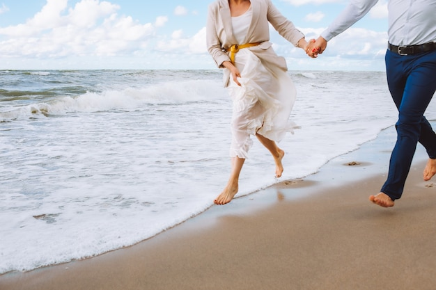 Happy just married unrecognizible middle age couple walk at beach and have fun on summer day.