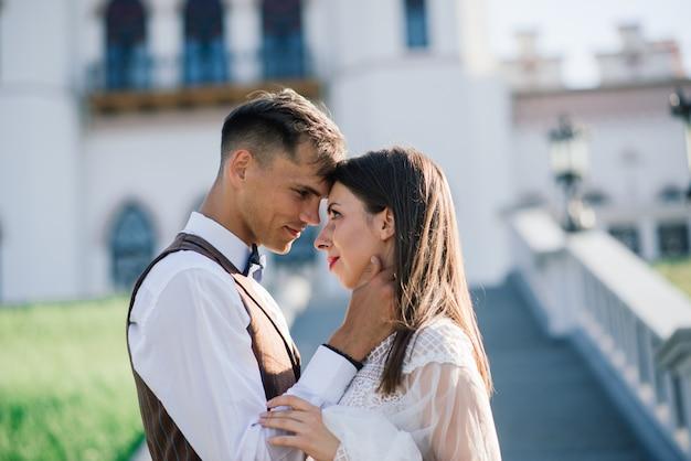 幸せなちょうど結婚されていた若いカップルを祝って、屋外で楽しんで