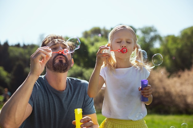 Happy kid. alert bearded father blowing soap bubbles with his daughter while relaxing in the park