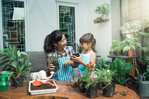 幸せな子供と母親の家でガーデニング