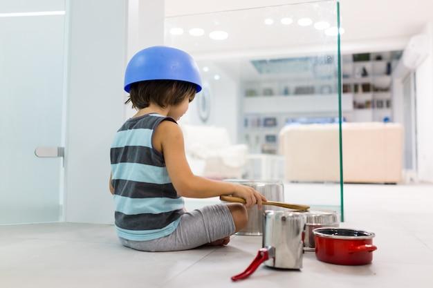 Счастливый ребенок дома играет с блюдами, как музыкальные инструменты и барабаны