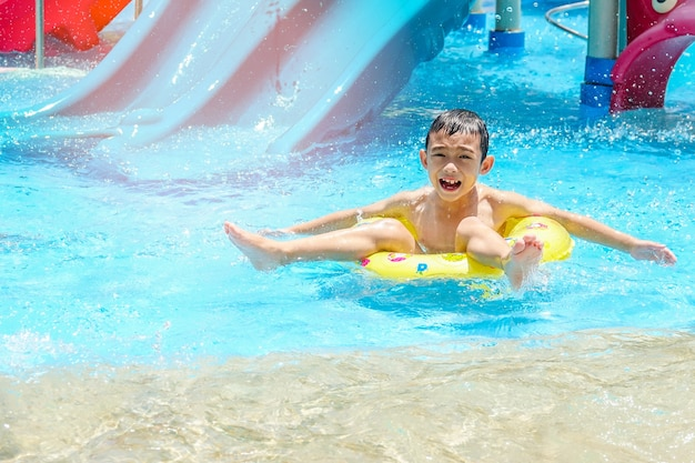Happy kid boy on safety ring in swimming pool