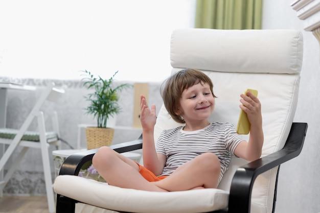 Счастливый ребенок мальчик сидит на компьютере, используя ноутбук и имея видеозвонок улыбающийся ребенок, сидящий дома