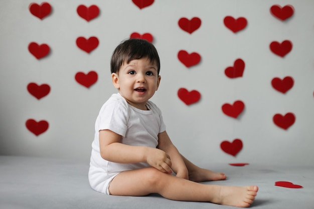 Happy kid boy in a white bodysuit with bow tie sits on a background of a gray wall with hearts on valentine's day.