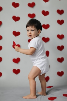 Happy kid boy in a white bodysuit with bow tie stands on the background of a gray wall with hearts on valentine's day.
