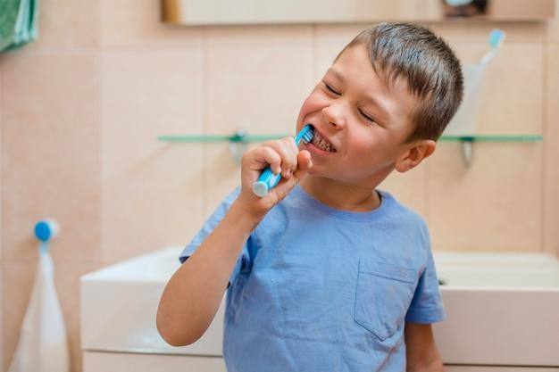 Happy kid or child brushing teeth in bathroom.