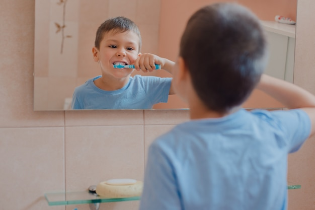 Happy kid or child brushing teeth in bathroom.