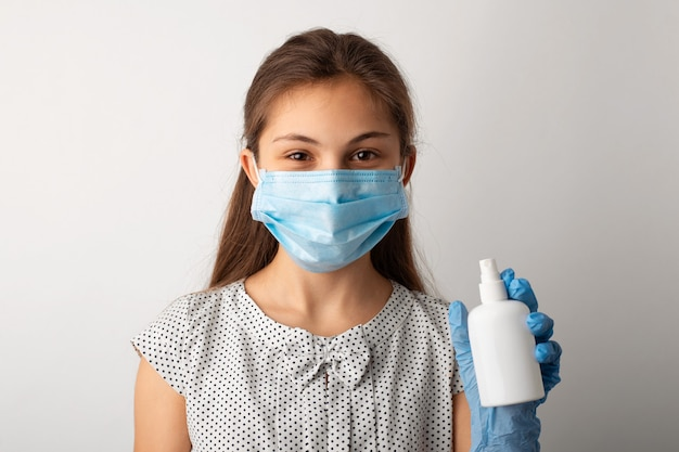 Счастливый ребенок, одетый в легкое платье, в защитной медицинской маске и перчатках, показывает бутылку с антибактериальным дезинфицирующим средством