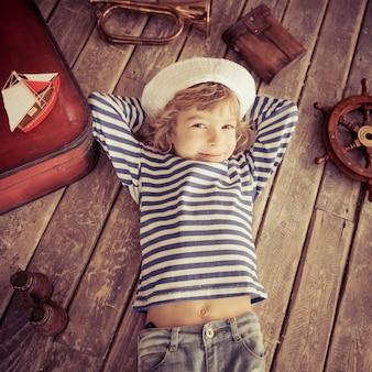 船乗りに身を包んだ幸せな子供。家で遊んでいる子供。旅行と冒険のコンセプト