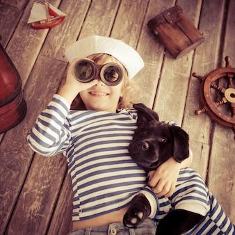 船乗りに身を包んだ幸せな子供。家で犬と遊ぶ子供。旅行と冒険のコンセプト