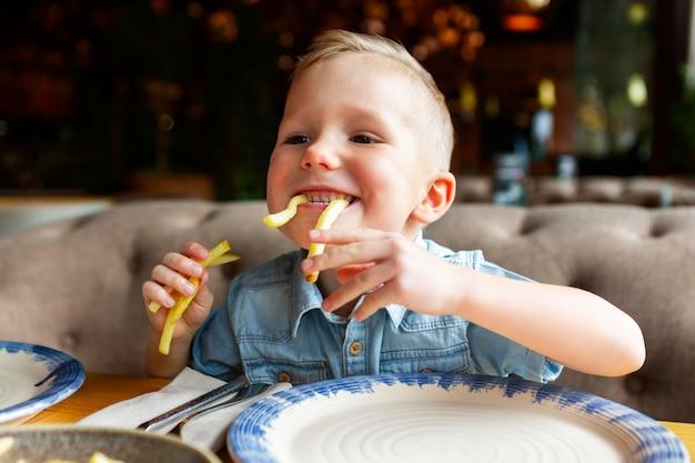 Bambino felice che mangia patatine fritte