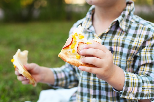 Happy kid eating pizza outdoors