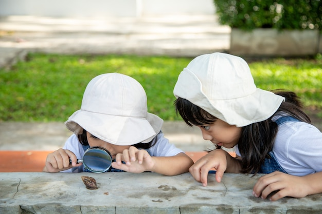 Счастливый ребенок девочка изучает природу с увеличительным стеклом и улиткой. он веселится в саду. концепция малыша готова пойти в школу.
