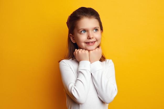 Счастливый ребенок девочка держит руки под подбородком и думает о чем-то приятном