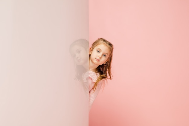 Happy kid, girl isolated on coral pink