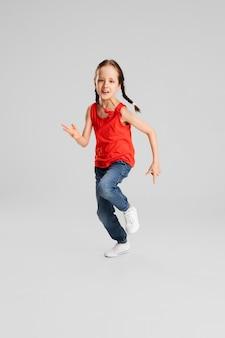 幸せな子供、白い壁に隔離された女の子。幸せ、陽気に見えます。コピースペース幼児期、教育、感情、ビジネス、表情のコンセプト。高くジャンプし、祝って走る