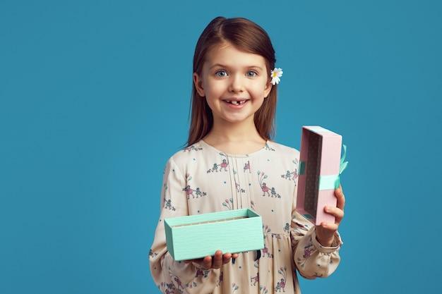 Счастливый ребенок девочка открывает подарочную коробку, изолированную на синей стене