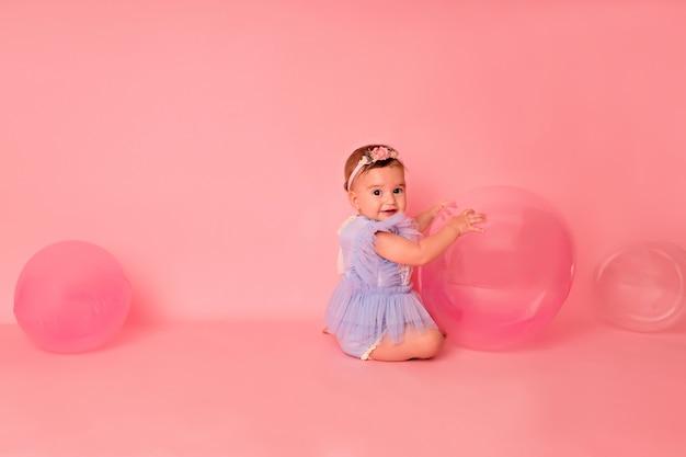 ピンクの背景に風船を持つ幸せな子供の女の子が彼女の最初の誕生日を祝う