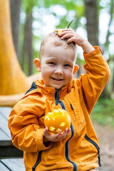 Happy kid having fun outdoors with carved pumpkin