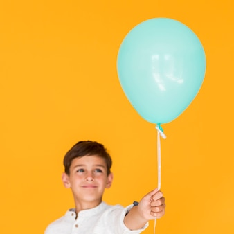 Happy kid holding a blue balloon
