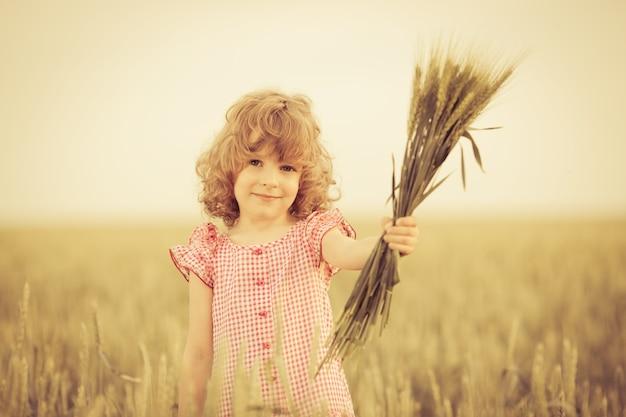 여름 필드에 밀을 들고 행복 한 아이