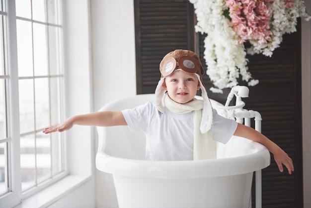 Счастливый малыш в пилотной шляпе, играя в ванной комнате. детство. фантазия, воображение.