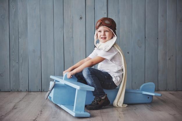 Счастливый малыш в пилотной шляпе, играя с деревянным самолетом против. детство. фантазия, воображение. праздничный день