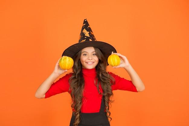 작은 노란색 호박, 할로윈 음식으로 할로윈 마녀 모자 의상을 입은 행복한 아이.