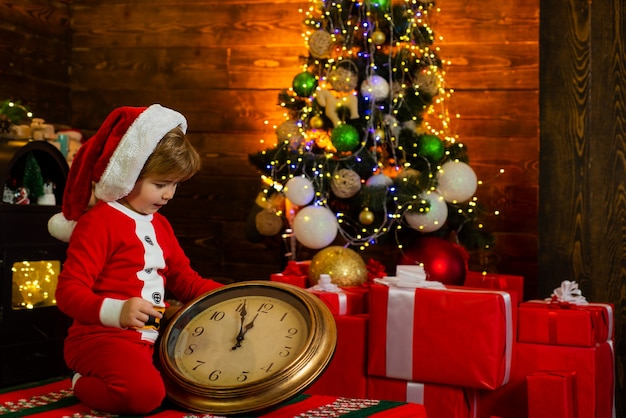 Happy kid is looking at the big clock in santa hat. kid is waiting for the new year. christmas concept. holidays. christmas child dreams.