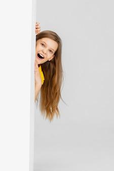 Il bambino felice isolato sulla parete bianca dello studio, sembra felice