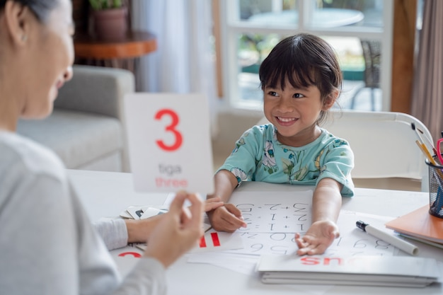 Happy kid learning and studying together with parent at home