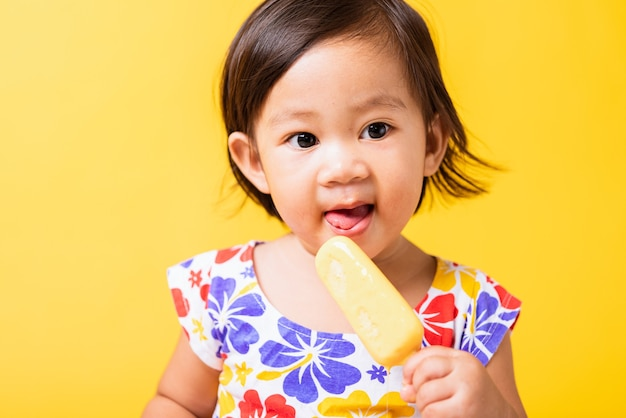Счастливый ребенок маленькая девочка смеется улыбка ест сладкое деревянное мороженое