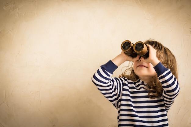 先を見据えて幸せな子供スパイグラス旅行と冒険のコンセプトで笑顔の子供