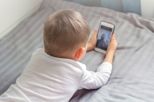 Happy kid make video call by smartphone to his dad. stay home, social distance and self-isolation during quarantine concept.