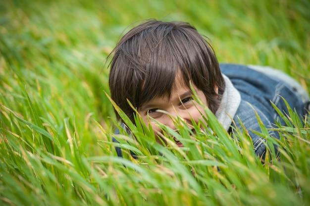 美しい緑色の黄色の草原でハッピーな子供
