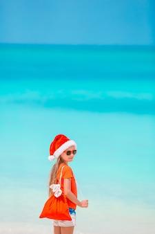 ビーチでのクリスマス休暇の幸せな子供 Premium写真