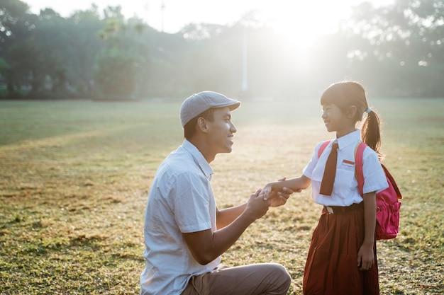 午前中に父親が連れて行った学校への初日の幸せな子供